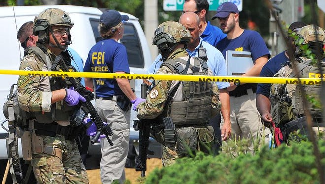 FBI, Orlando Police Department and the Orange County Sheriff's Office personnel investigate the attack at the Pulse nightclub  in Orlando Fla., Sunday, June 12, 2016. A gunman wielding an assault-type rifle and a handgun opened fire inside a crowded gay nightclub in Orlando, Fla.,early Sunday, before dying in a gunfight with SWAT officers, police said. It was the worst mass shooting in American history.  (Craig Rubadoux/Florida Today via AP)