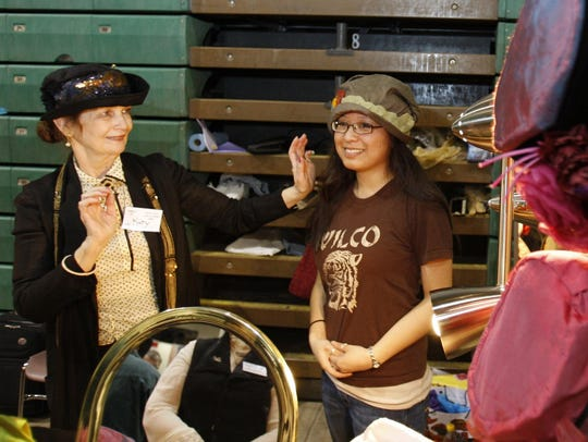 Katy Brennan helps Jessica Pace try on vintage hats