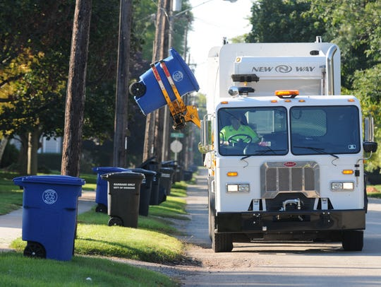 A city truck picks up recycling on the north side of