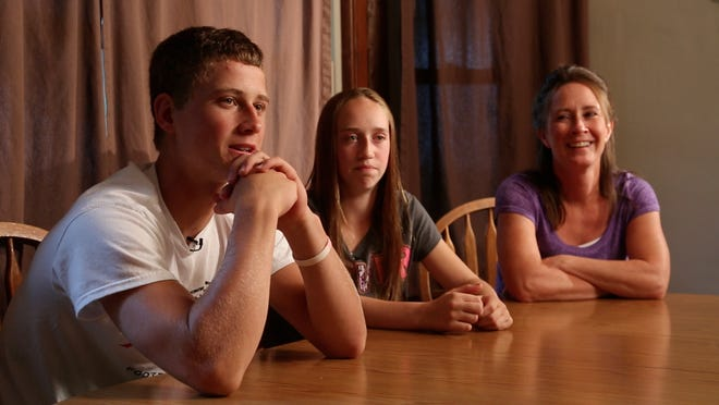 Esden Carroll talks with his sister Chloe and mother Sheryl at the family's home in LuVerne on Aug. 15.