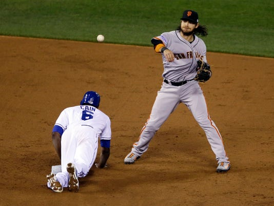 Kansas City Royals' Lorenzo Cain (6) is out at second as San Francisco Giants' Brandon Crawford turns a double play on a ball hit by Eric Hosmer during the third inning of Game 7 of baseball's World Series Wednesday, Oct. 29, 2014, in Kansas City, Mo. (AP Photo/Jeff Roberson)