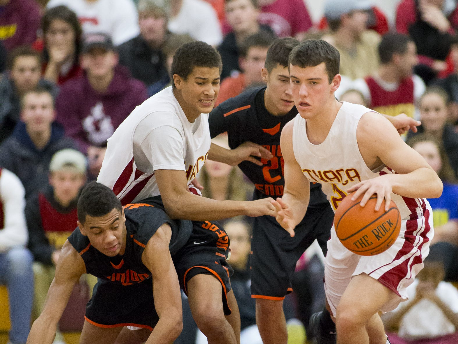 From left, Union-Endicott's Zac Camber tangles with Ithaca's Jordan Ayers while U-E's Snowden Vose looks to pursue Ithaca's Caleb Klausner up the court has he takes away loose ball in a game last year. The Little Red are looking to improve on last year's record, in which they netted 11 wins.