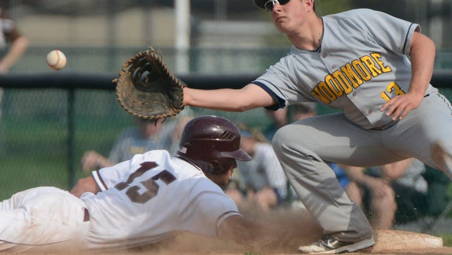 Genoa's Matt Aumiller is safe sliding back to first base past Woodmore's Dillon Williams in the second inning.
