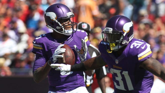 Minnesota Vikings running back Jerick McKinnon (31) protects for quarterback Teddy Bridgewater (5) during the second half of an NFL football game against the Tampa Bay Buccaneers on Sunday, Oct. 26, 2014, in Tampa, Fla. The Vikings won 19-13. (AP Photo/Reinhold Matay)