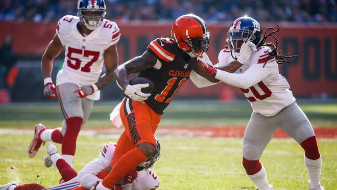 Cleveland Browns wide receiver Terrelle Pryor (11) runs against New York Giants cornerback Janoris Jenkins (20) as he is wrapped up by free safety Nat Berhe, lower, in the first half of an NFL football game, Sunday, Nov. 27, 2016, in Cleveland.