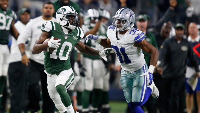 New York Jets wide receiver Kenbrell Thompkins (10) is chased by Dallas Cowboys free safety Byron Jones (31) after making a catch in the fourth quarter at AT&T Stadium. New York won 19-16.