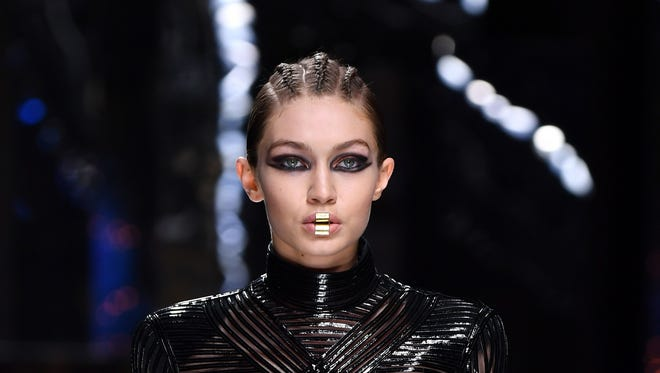 Gigi Hadid, seen here walking in the Balmain show at Paris Fashion Week Wednesday, strikes a  different look on the cover of 'Vogue Arabia.'