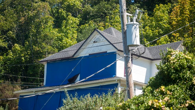 """In this photo taken on Aug. 17, 2015, the home featured in the 1985 classic """"The Goonies"""" is covered in blue tarps to deter fans from getting too close to the house, in Astoria, Ore. The home gets up to 1,500 visitors daily, and the property owner is asking for relief.  (Joshua Bessex /Daily Astorian via AP) MANDATORY CREDIT"""