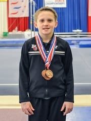 Brock Buffington, age 11, stands with his medals from the 2016 PA State Championships. He placed third on high bar, fifth on rings and vault, and was 10th all-around.