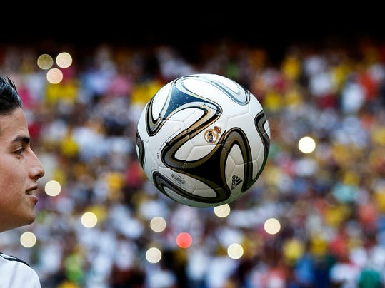 New Real Madrid player James Rodriguez, from Colombia, plays with a ball as he poses for photographers during his official presentation at the Santiago Bernabeu stadium in Madrid, Spain, Tuesday, July 22, 2014, after signing for Real Madrid. Real Madrid have signed Rodriguez from Monaco on a six-year contract,  (AP Photo/Daniel Ochoa de Olza)