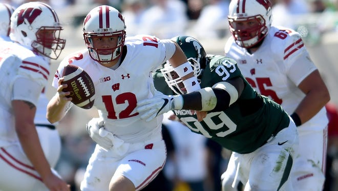 Alex Hornibrook of the Wisconsin Badgers is grabbed by Raequan Williams (99) of the Michigan State Spartans on Sept. 24, 2016, in East Lansing.
