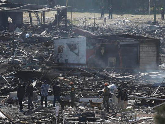 Soldiers and investigators walk through the scorched rubble of the open-air San Pablito fireworks market in Tultepec on the outskirts of Mexico City, Wednesday, Dec. 21, 2016. The market was especially well stocked for the holidays and bustling with hundreds of shoppers when a powerful chain-reaction explosion ripped through its stalls Tuesday, killing and injuring dozens.