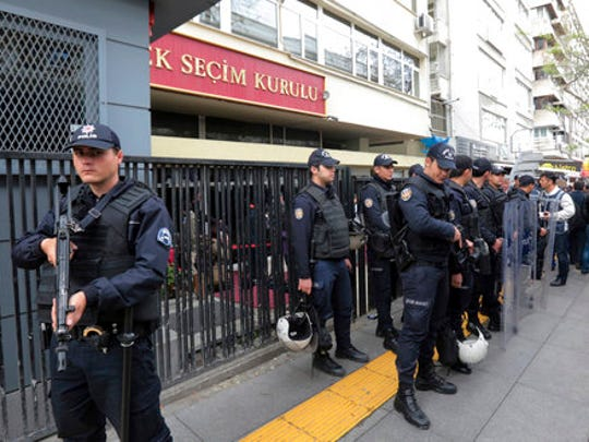 Riot police stand guard as people queue in front of Turkey's Supreme Electoral Board in Ankara, Turkey, Tuesday, April 18, 2017. Turkey's prime minister on Tuesday called on the opposition to respect the result of a referendum that will give sweeping new powers to the office of the president, but the main opposition party formally requested the vote be annulled.