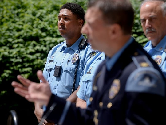 Lansing Police Officer David Burke wears one of three body cameras the department is testing Monday, June 1, 2015 as he stands and listens to Police Chief Michael Yankowski during a press conference where officials announced the start of the pilot project.