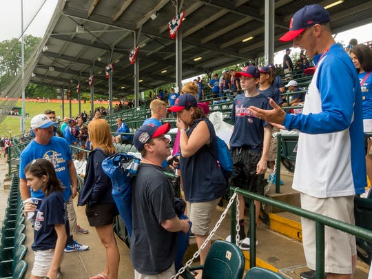Steve Hamlin, center, talks to Jude Abbadessa's father, Vince, right, as Maine-Endwell Little League parents and supporters talk in the stands after play was called off for the day after heavy rain.  Hamlin is a teacher of Jude Abbadessa at Jennie F. Snapp Middle School in the Union- Endicott district.