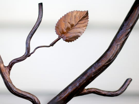 A display shows customers a railing that contains a leaf and branch at Specialty Iron Works.
