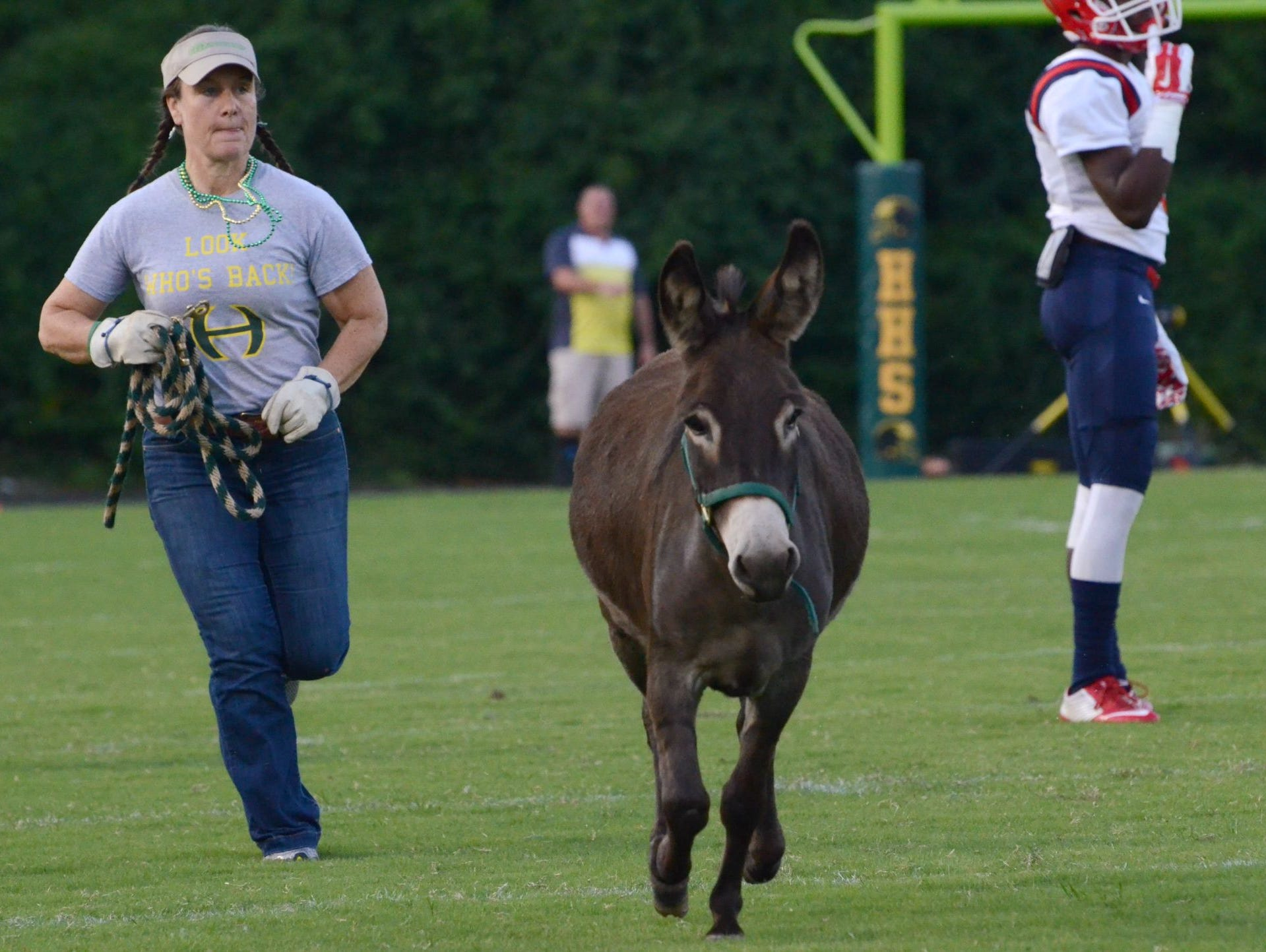 Becky Sharpe, left, escorts on of Hillsboro's two mascots, Xote, prior to the Burros' Week 2 matchup with Oakland.