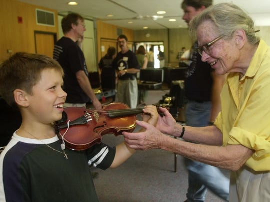Carolyn Long helps Sam Martin, 8, of Burlington try out a violin during the 27th Annual Intrument Sale to benefit the Vermont Youth Orchestra Association in 2001.