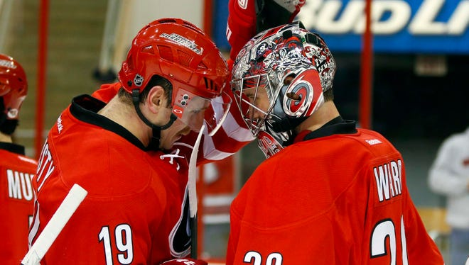 Carolina Hurricanes goalie Cam Ward  is congratulated by forward Jiri Tlusty after defeating the Ottawa Senators 4-1.