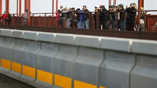 Pedestrians and bicyclists watch a road crew install the movable median barrier on the Golden Gate Bridge in San Francisco, on Saturday, Jan 10, 2015. The span is scheduled to reopen at 4 a.m. Monday once the work is completed and the system has been fully tested. (AP Photo/San Francisco Chronicle, Paul Chinn)  MANDATORY CREDIT PHOTOG & CHRONICLE; MAGS OUT; NO SALES