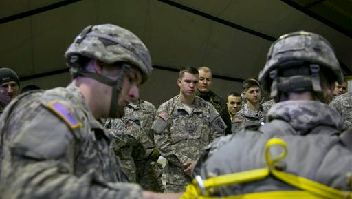 U.S Army soldiers of the 4th Infantry Brigade, Combat team (Airborne) 25th Infantry Division, part of the NATO-led peacekeeping mission in Kosovo watch as a jump master gives a demonstration on  preparing their gear for a parachute training exercise in U.S military base Camp Bondsteel, near the village of Sojeve in Kosovo, Sunday, Dec. 21, 2014. The U.S Army peacekeeping force regularly conducts parachute exercises to maintain proficiency in airborne operations during their deployment in Kosovo.  (AP Photo/Visar Kryeziu)