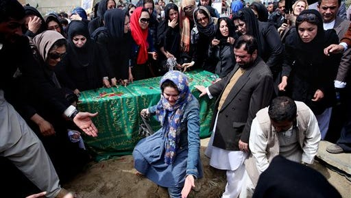Hundreds of women's rights activists and others gather around the coffin of 27-year-old Farkhunda, an Afghan woman who was beaten to death by a mob, during her funeral, in Kabul, Afghanistan, on Sunday, March 22, 2015.  Farkhunda, who like many Afghans is known by only one name,  was killed late Thursday by a mob of mostly men who beat her, set her body on fire and then threw it into the Kabul River, according to police accounts. Police are still investigating what prompted the assault.