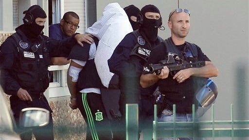 The suspect in the beheading of a businessman, Yassine Salhi, a towel over his head to mask his face, is escorted by police officers as they leave his home in Saint-Priest, outside the city of Lyon, central France, Sunday, June 28, 2015. A security official tells The Associated Press the move to his home aims to find his passport, to determine if he traveled abroad. The suspect allegedly crashed a truck into a U.S.-owned chemical warehouse on Friday, setting off an explosion, and hung his employer's head on the factory's gate. (AP Photo/Laurent Cipriani)