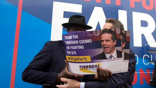 New York Gov. Andrew Cuomo, right, talks with Henry Singleton, of 1199 SEIU, before a rally to raise the minimum wage on Thursday, Feb. 25, 2016, in Albany, N.Y.