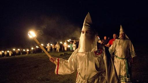 "In this Saturday, April 23, 2016 photo, members of the Ku Klux Klan participate in cross burnings after a ""white pride"" rally in rural Paulding County near Cedar Town, Ga. Born in the ashes of the smoldering South after the Civil War, the KKK died and was reborn before losing the fight against civil rights in the 1960s. Membership dwindled, a unified group fractured, and one-time members went to prison for a string of murderous attacks against blacks. Many assumed the group was dead, a white-robed ghost of hate and violence."