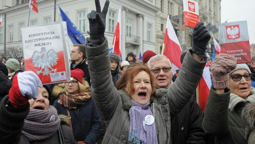 Protesters holding copies of Poland's constitution shout slogans during an anti-government demonstration, in Warsaw, Poland, Saturday, Dec. 17, 2016. Opponents of the country's populist government are staging a new protest outside the presidential palace in an appeal to the head of state to protect the young democracy's constitutional order from a series of government steps they deem anti-democratic.