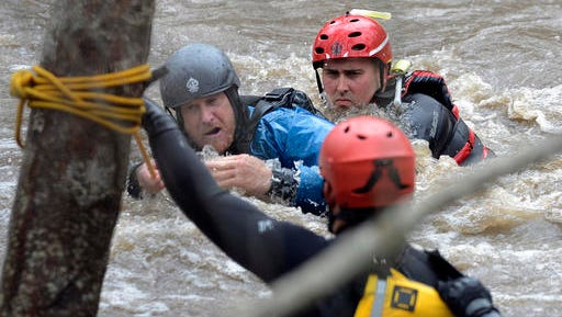 Jason Williams, left, is rescued by Calfire rescue swimmer Danny Ciecek after Williams got snagged on trees while trying to kayak the Carmel River with a friend near Paso Hondo Road in Carmel Valley on Monday, Jan. 9, 2017, after a large storm passed through Monterey County.