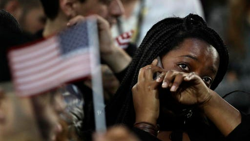 FILE - In this Nov. 8, 2016 file photo, a woman weeps as election results are reported during Democratic presidential nominee Hillary Clinton's election night rally in the Jacob Javits Center glass enclosed lobby in New York.  As Donald Trump approaches his inauguration as president, young Americans have a deeply pessimistic view about his incoming administration, with young blacks, Latinos and Asian Americans particularly concerned about what's to come in the next four years.