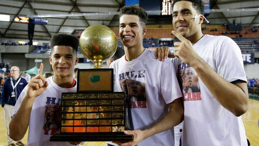 Nathan Hale forward Michael Porter Jr., center, poses with his brothers, Coban Porter, left, and Jontay Porter, right, with the trophy after Nathan Hale defeated Garfield 68-51 to win the boys' Class 3A high school basketball championship, Saturday, March 4, 2017, in Tacoma, Wash. (AP Photo/Ted S. Warren)