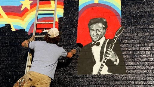 Joe Albanese replaces an old mural with a new painting that will feature the album cover of a new Chuck Berry album at Delmar Loop in St. Louis on Saturday, March 18, 2017. They were surprised to hear that the music legend died as they were working on the project. Earlier in the day, police announced Berry died at the age of 90.