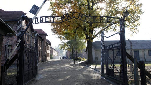 """File - In this Oct. 19, 2012 file photo the entrance with the inscription """"Arbeit Macht Frei"""" (Work Sets You Free) gate of the former German Nazi death camp of Auschwitz is seen at the Auschwitz-Birkenau memorial in Oswiecim, Poland. A group of nearly a dozen people took off their clothes, killed a sheep and chained themselves together by the gate before being detained by police, Friday, March 24, 2017."""