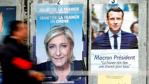 A man walks past electoral posters of French centrist presidential candidate Emmanuel Macron, right, and far-right candidate Marine Le Pen in Saint Jean de Luz, southwestern France, Wednesday, April 26.
