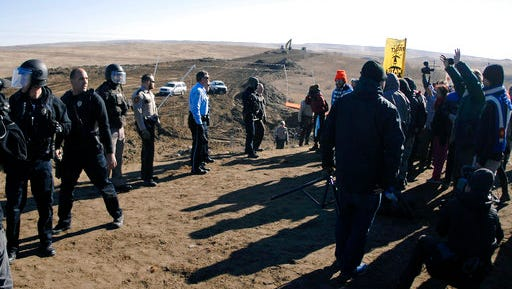 FILE - In this Nov. 11, 2016, file photo, law enforcement personnel try to move Dakota Access pipeline protesters further down during a protest at a pipeline construction site south of St. Anthony, N.D. North Dakota Gov. Doug Burgum emailed President Donald Trump on Saturday, April 29, 2017, seeking a presidential disaster declaration to pave the way for federal aid related to months of protests over construction of the pipeline.