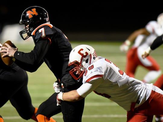 Northville quarterback Jack Burke (left) tries to avoid