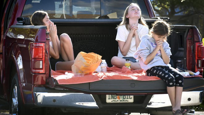 Callie Cyr, 12, (left) Grace Lovell, 12, and Kinsey Cyr, 10 (front ) pray during the service.  First United Methodist Church Jupiter-Tequesta has a creative strategy to hold church on Sunday morning, March 22, 2020, a drive-in service. The church has its own FM radio frequency that parishioners can tune into and cars can fan out over the church's east parking lot.