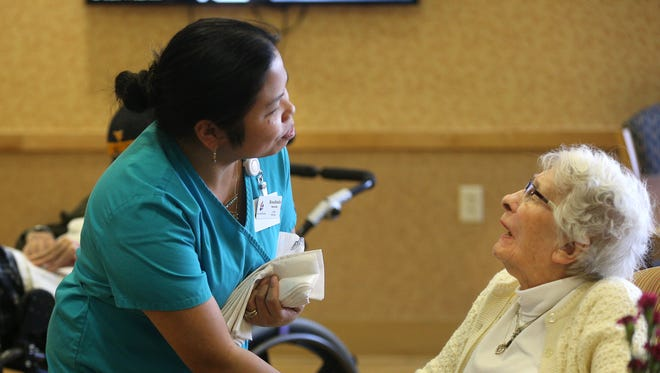Rosalinda MAchado (left) a certified nursing assistant at  Jewish Senior Living gets a resident ready for lunch. Staff at the facility are happy for the chance to have flexible schedules.