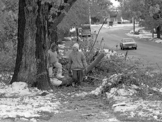 Two girls make their way through downed tree branches,