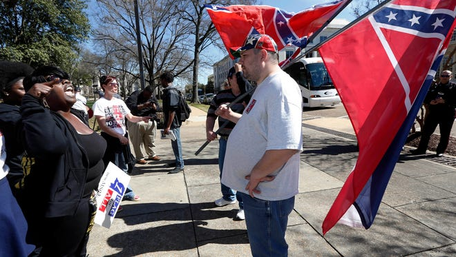 Wanda Bingham of Laurel, left, who supports the removal of the Confederate battle emblem from the Mississippi state flag, argues with Craig Haden of Braxton, who wants to keep the emblem on the flag, following a rally to remove the emblem at the state Capitol in Jackson on Thursday, Feb. 18, 2016. A diverse group of about 200 people took part in the rally as lawmakers worked inside. The event attracted roughly the same number of people as a mostly white keep-the-flag rally that took place in the same spot in January.