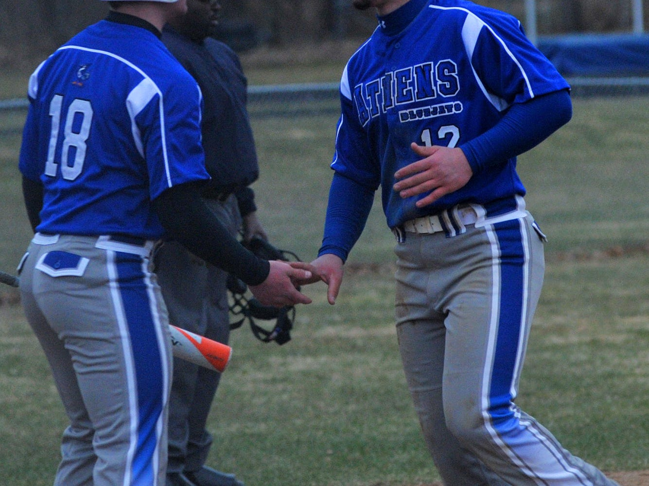 Athens' Lane Tessmer, right, is congratulated by teammate Max Stange after scoring a run in the fourth inning Tuesday against Chequamegon in Athens.