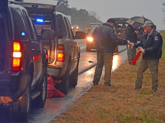 Investigators collect evidence at the scene of a shooting on Interstate 85 early Wednesday morning.