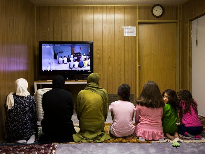 Sarah, 5, looks back as women pray the Maghrib prayer