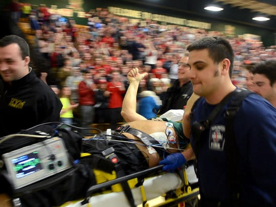 Free Press Visuals Coach Ryan Mercer won the top sports photo award for this image of Rice Memorial High School girls basketball coach Tim Rice giving a thumbs at Patrick Gym  early in 2015 as he was taken to the hospital on a stretcher. Minutes earlier, Rice had collapsed courtside.