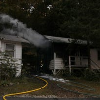 Firefighters battle a blaze at a cabin at the Omega Institute on Sunday morning.