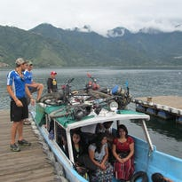 Kai Ashland, left, and Coralville's Jon Williams ponder the security of their bikes strapped to the roof of this water taxi on Lake Atitlan in Guatemala as they head for Guatemala City.