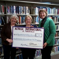 Darlene Krake, at left, and Jennifer Lurvey, at right, present a check of $1,265 to Lori Belongia, director of the Marshfield Public Library, on behalf of Altrusa Club of Marshfield. The donation is a result of monies raised through the 2014 Holiday Home Tour sponsored by Altrusa in support of literacy. This year's funds were designated for three library projects Battle of the Books, 1000 Books by Kindergarten, and ABC Computer and Technology classes.