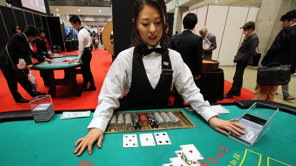 A dealer demonstrates how to play blackjack at a leisure exhibition in Tokyo in November 2014.
